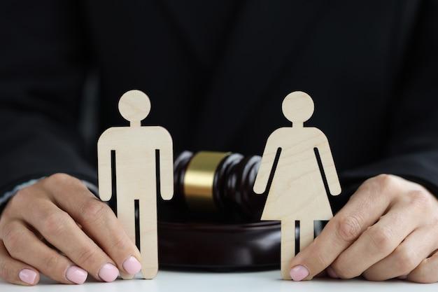 Деревянные фигуры мужчины и женщины в руках судьи на фоне концепции молотка судьи