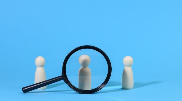 남자의 나무 인물은 파란색 배경과 검은색 돋보기에 서 있습니다. 채용 개념, 재능 있고 유능한 직원 검색, 경력 성장