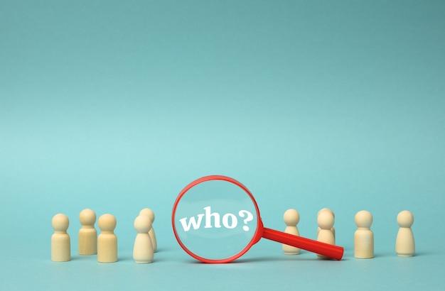 На синем фоне стоят деревянные фигурки мужчин и пластиковая лупа. концепция подбора персонала, поиск талантливых и способных сотрудников, карьерный рост