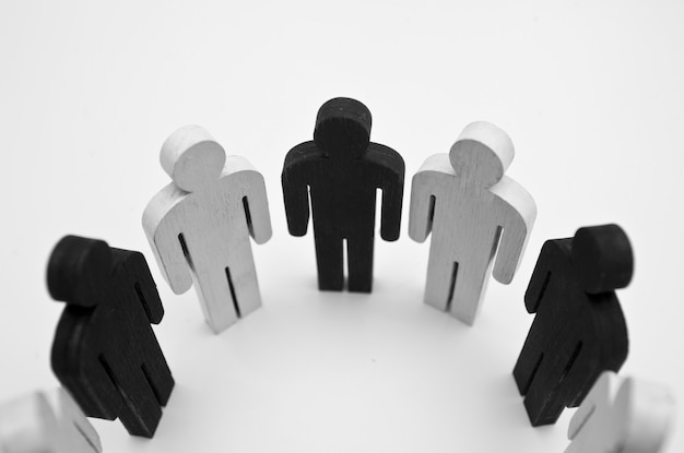 黒と白の人の木像が円を描くように立っています。友情、チームワーク、人種差別の欠如の概念