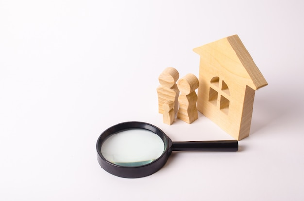 Wooden figures of people are standing near a wooden house and a magnifying glass.