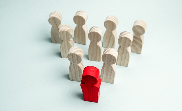 Wooden figures of people. the boss of the business team indicates the direction of movement