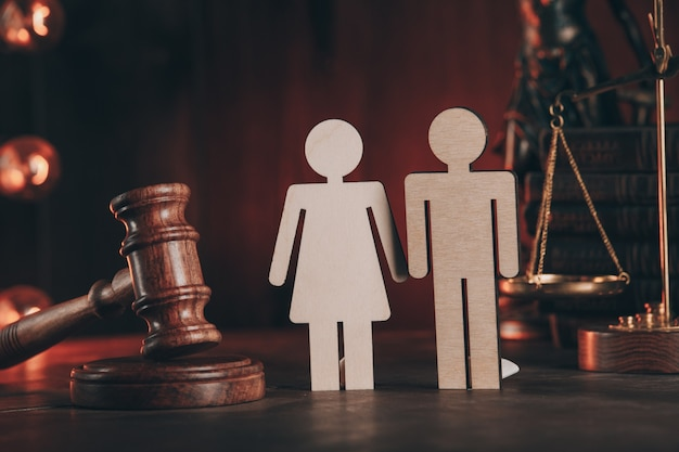 Wooden figures of people and gavel on a table