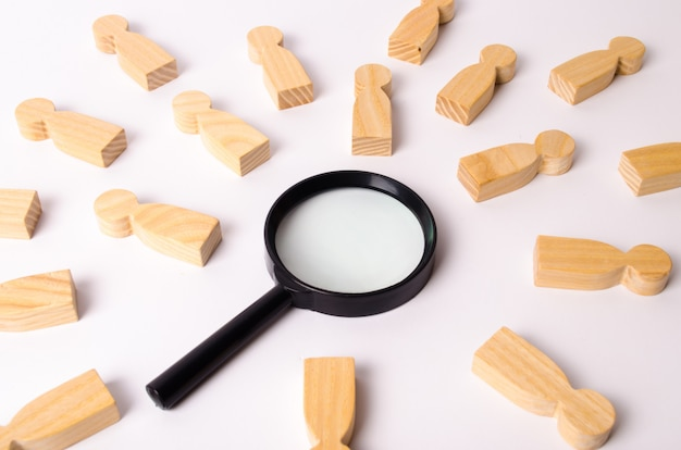 Wooden figures of people lie around a magnifying glass on a white background.