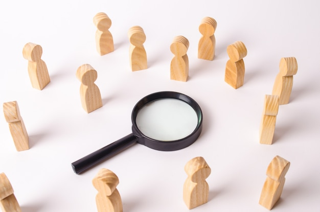 Wooden figures of people stand around the magnifying glass and look to the center.