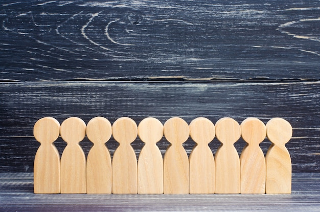 Wooden figures of people stand in a row in the formation on the background of ebony.
