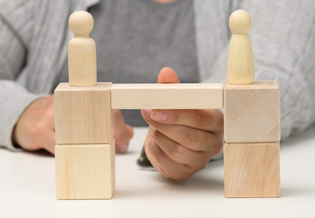 Wooden figures stand on the bridge from the sides opposite each other, concept of finding a compromise, constructive dialogue, business opponents