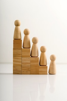 Wooden figures stand on the cubes that represent the stairs.