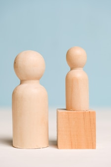Wooden figures with a cube on a blue background. mentoring concept. a professional teaches a student. close up.