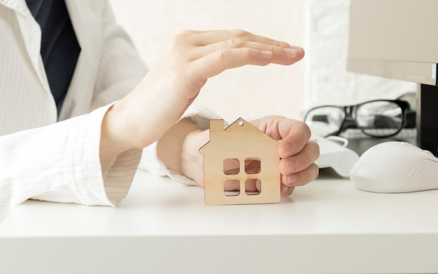 Wooden figurine of house in female hand on bright background