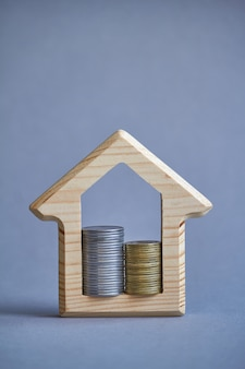 Wooden figurine of house and two columns of coins inside on gray background.