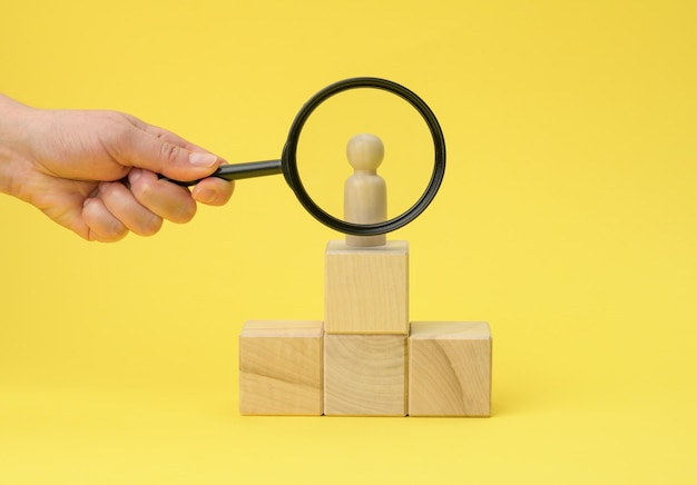 Wooden figurine of a man on a pedestal and a hand with a magnifying glass on a yellow surface
