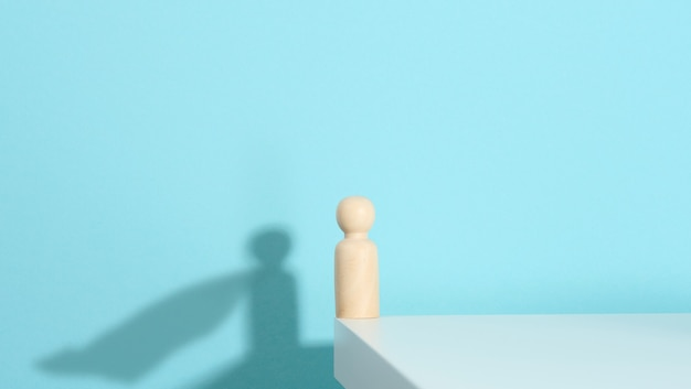Wooden figurine of a man and a shadow with a developing cloak, the concept of the strong and the winner. everyone is stronger than he thinks, a superhero. blue background