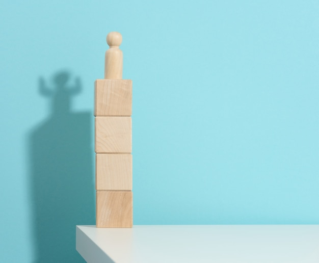Wooden figurine of a man stands high on the cubes, the shadow of a strong and victorious. everyone is stronger than he thinks, a superhero. blue background