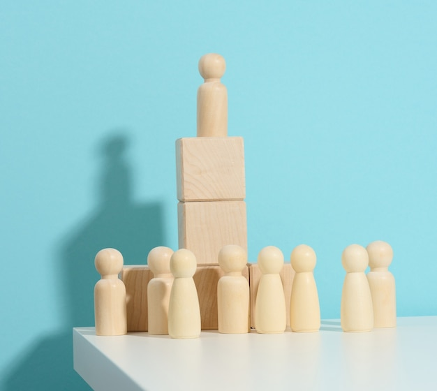 Wooden figurine of a man stands on a high podium of cubes, below the crowd. search for talented employees, rally, manipulation of the masses, selection of employees for the team