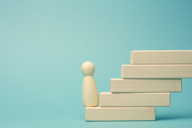 A wooden figurine of a man stands on a staircase made of blocks on the first step. the concept of achieving the set goals in business, career growth, start-up