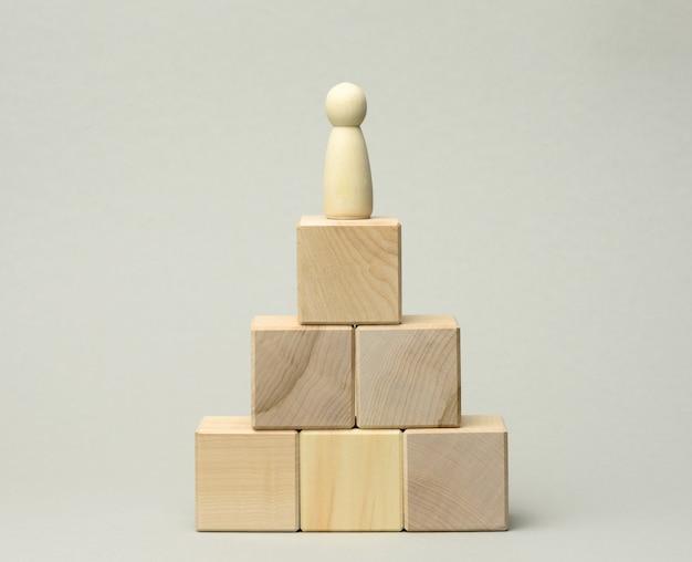 피라미드 꼭대기에있는 남자의 나무 입상
