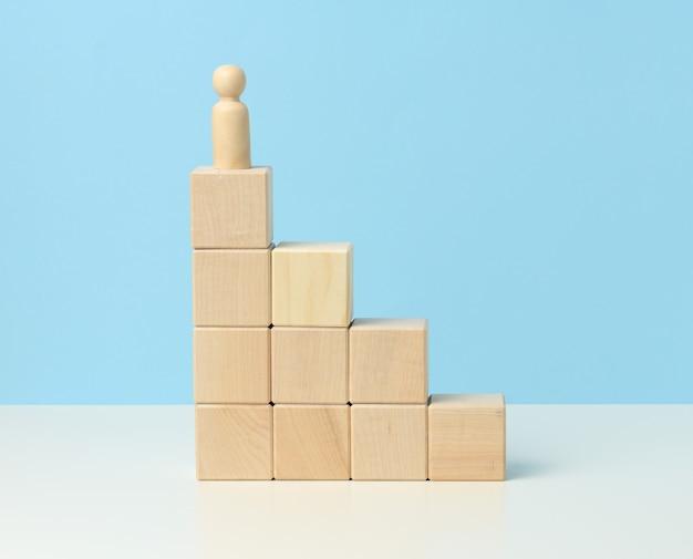 木製の立方体の上に男の木製の置物。目的意識、目標の達成、障害の克服の概念