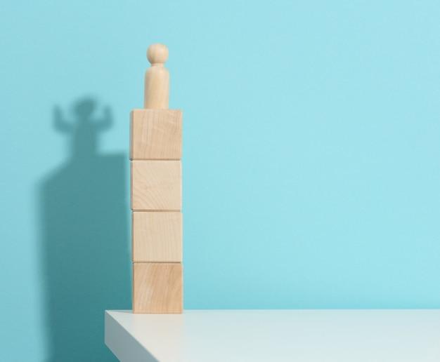 남자의 나무 입상은 강하고 승리하는 사람의 그림자인 큐브 위에 높이 서 있습니다. 모두가 생각보다 강하다, 슈퍼히어로. 파란색 배경
