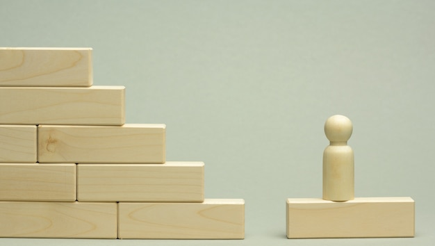 남자의 나무 입상은 첫 번째 단계에서 블록으로 만든 계단에 선다. 비즈니스, 경력 성장, 스타트 업에서 설정된 목표를 달성하는 개념