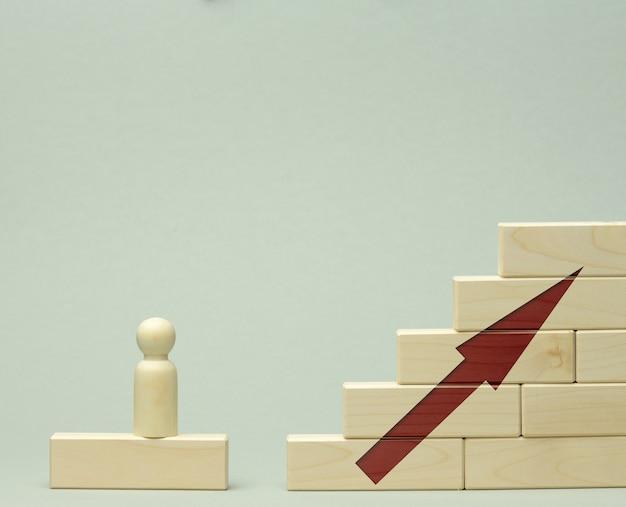 最初のステップでブロックで作られた階段に立っている男の木製の置物