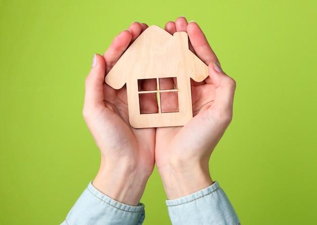 緑の上の女性の手で家の木製の置物