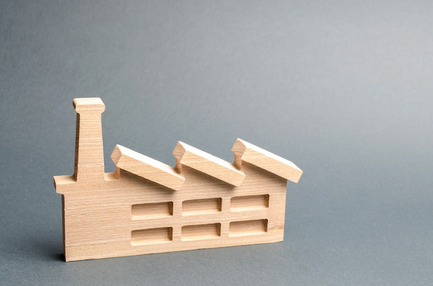Wooden figurine of a plant or factory on gray. recycling raw materials