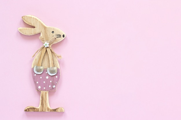 Wooden figurine rabbit on pink paper background concept valentine's card or happy easter card