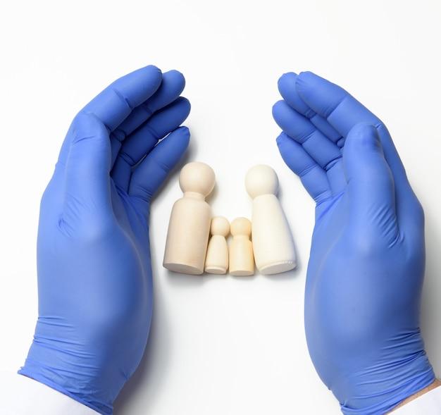 Деревянные фигурки папа, мама и двое детей, руки доктора в синих перчатках защищают, концепция страхования