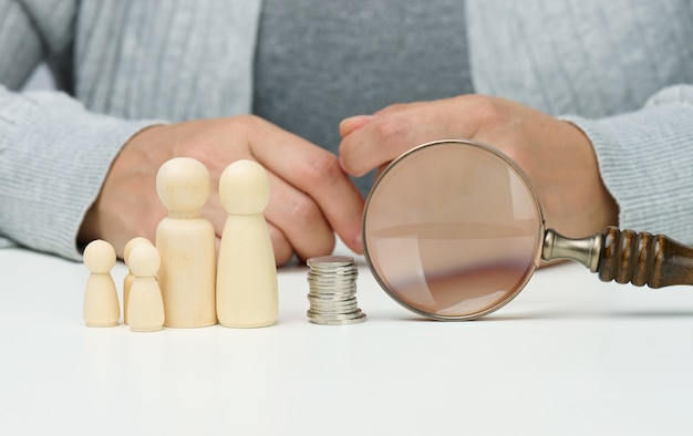 Wooden figurines of a family and magnifier and white coins on the white table. income growth concept, high percentage of investment. search for new sources of income, subsidy