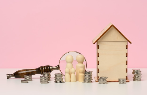 Wooden figurines of a family, stacks of metal money, a miniature wooden house. real estate purchase, mortgage concept. accumulation of funds