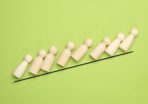 남자 모양의 나무 인형은 녹색 배경, 리더십 개념에 가파른 선을 올라