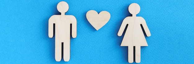 Wooden figurines of man and woman with heart on blue background