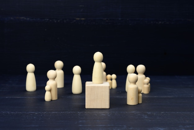 Wooden figurines of men on a blue surface
