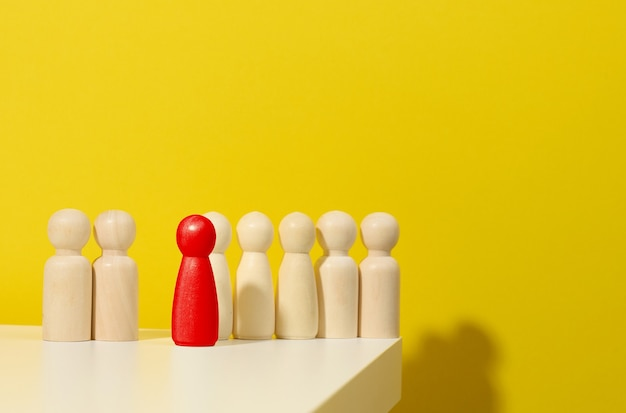 Wooden figurines of men and one red on a blue background. leader and recruiting concept. toxic personality in the team