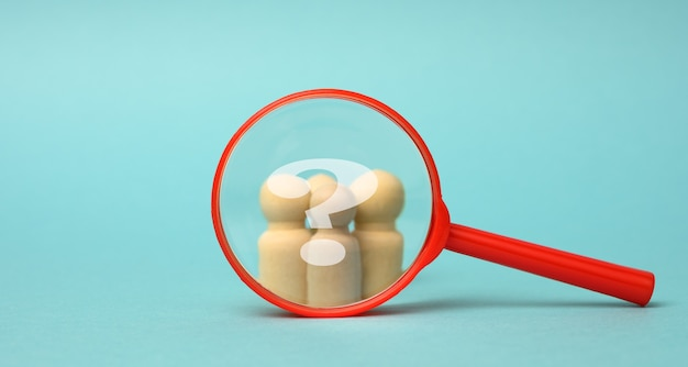Wooden figurines of men and a red magnifying glass on a blue background. recruitment for the company, like-minded people and teamwork. search for talent
