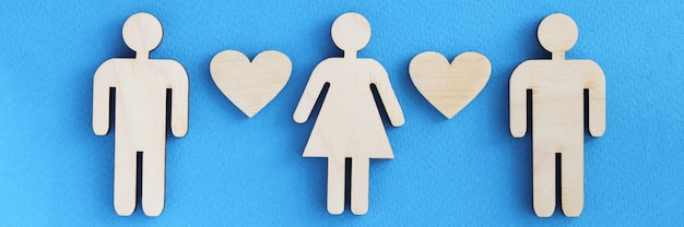 Wooden figurines of men and women with hearts on blue background