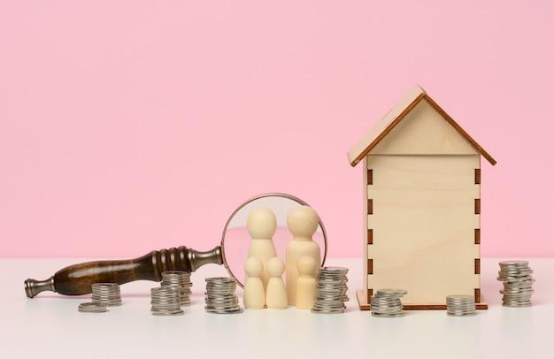 가족의 나무 인형, 금속 화폐 더미, 소형 목조 주택. 부동산 구매, 모기지 개념입니다. 자금의 축적