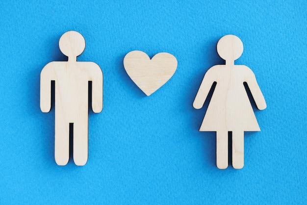 青い表面にハートを持つ男性と女性の木製の置物