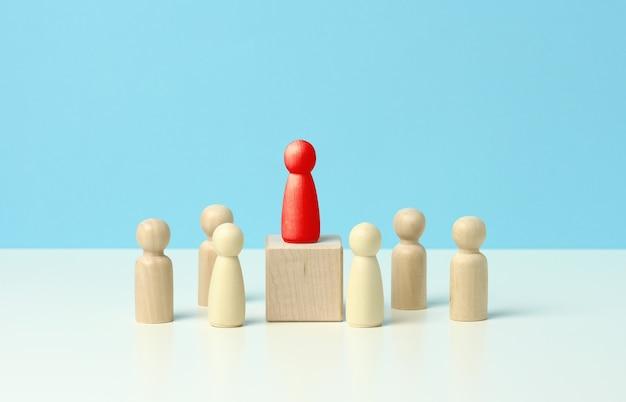 Деревянные фигурки мужчин на синем фоне. концепция публичных выступлений, лидерство и обсуждение. команда объединяется вокруг идеи, сотрудничества