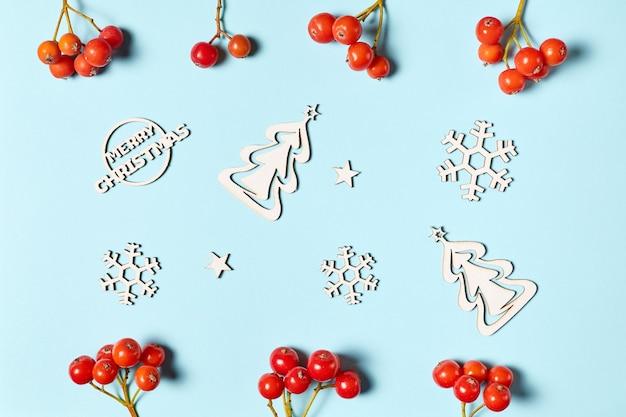 Деревянные фигурки снежинок и елок на синем фоне, украшенные ягодами рябины