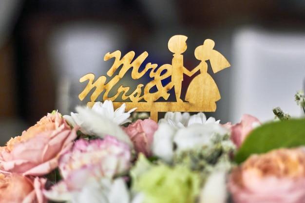 Деревянные фигурки жениха и невесты в обрамлении свадебных цветов