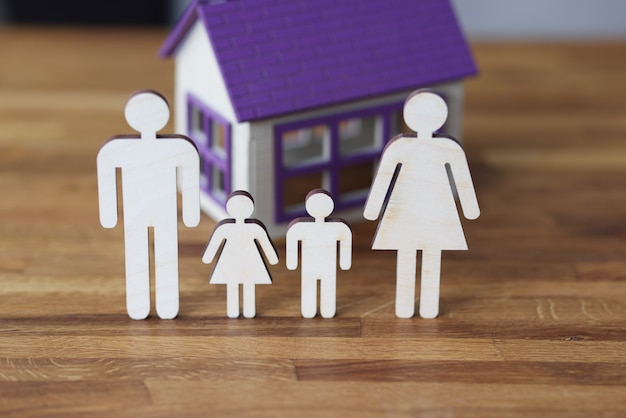 Wooden figurines of parents and children on background of house