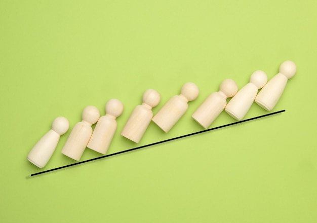 Wooden figurines in the shape of a man climb up a steep line on a green background, leadership concept