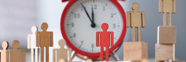 알람 시계 옆에 하나의 빨간색 그림 스탠드가 있는 나무 인형