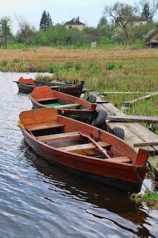 Деревянная рыбацкая лодка. старая лодка с отражением в воде на реке, латвия.
