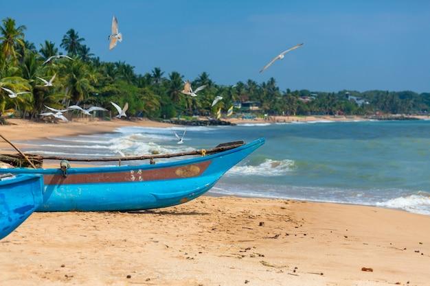 Деревянная рыбацкая лодка на берегу океана. рыбацкая деревня на острове.