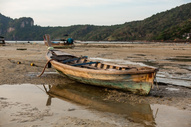 A wooden fishing boat sat on the sandy bottom of the ocean at low tide.
