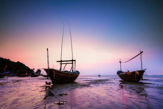 Wooden fishing boat on sea beach at sunset.