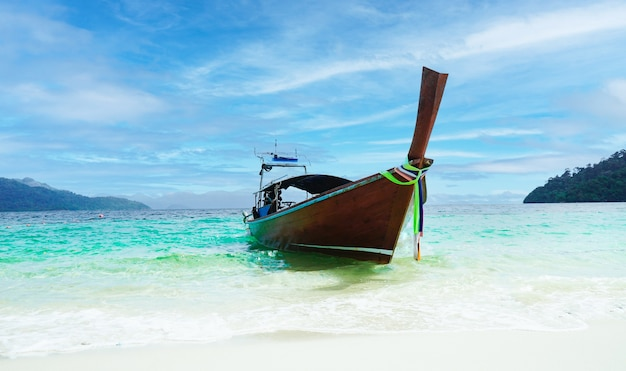Wooden fishing boat on sea coast of tropical lipe island in thailand at sunny day of summer vacations